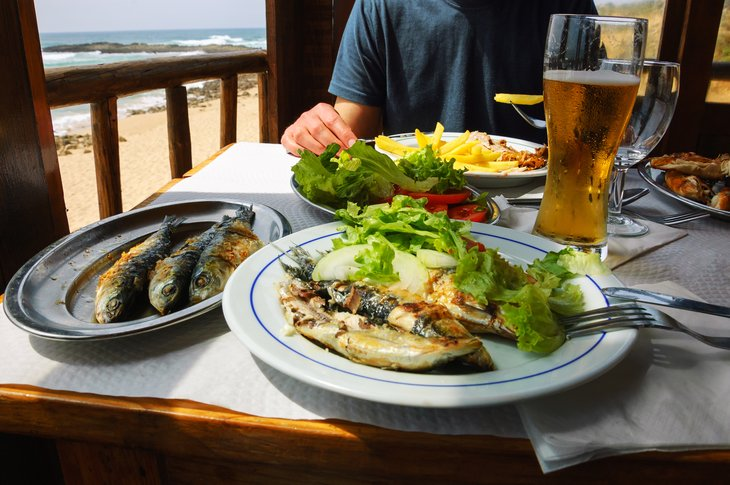 restaurant specialty Traditional Portuguese lunch - grilled sardines and chicken - at restaurant terrace with ocean beach view. Algarve, Portugal