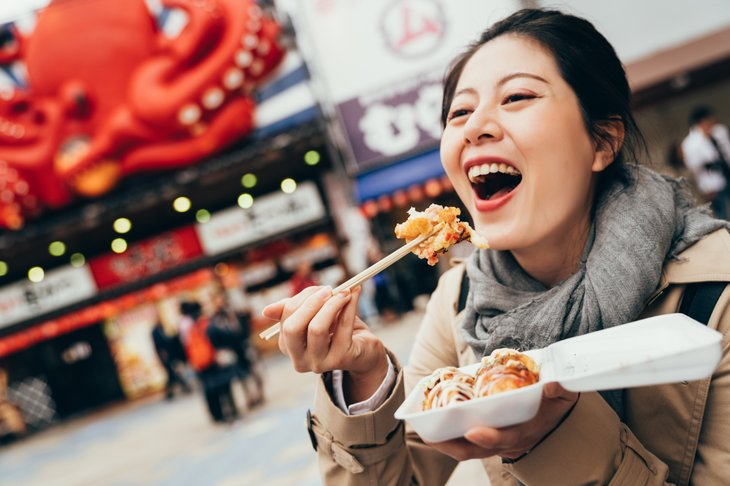 cheerful lady tourist girl backpacker laughing eating octopus chopsticks outdoor. young woman holding box street food