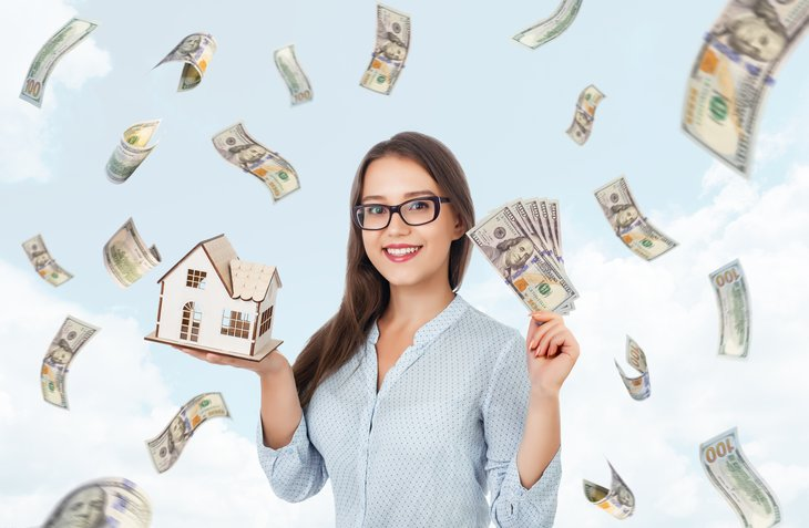 Young woman holding cash, model of a home.