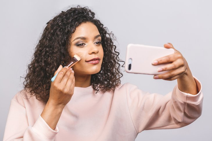 Close up side portrait of beautiful african american woman applying makeup with brush. make up liquid foundation Using phone