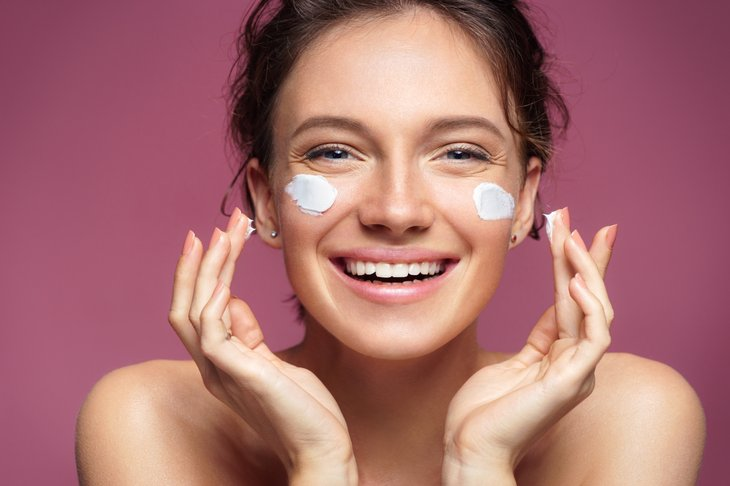Laughing woman girl applying moisturizing skin cream on her face. skin care pink background.