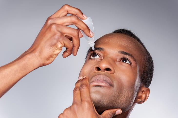 African american man applying eye drops