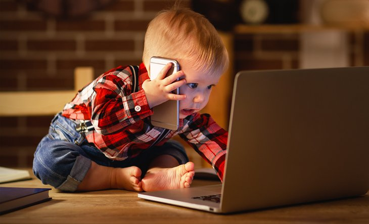 A baby uses a smartphone and laptop computer