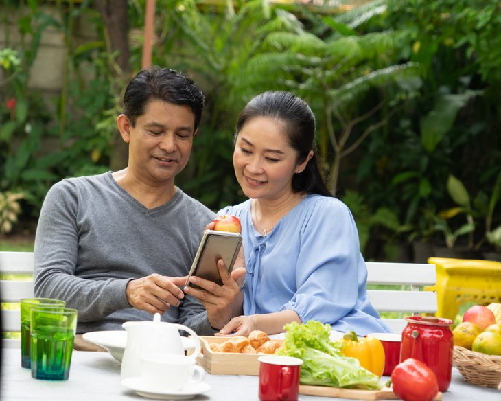 Asian senior man woman couple looking at phone home garden