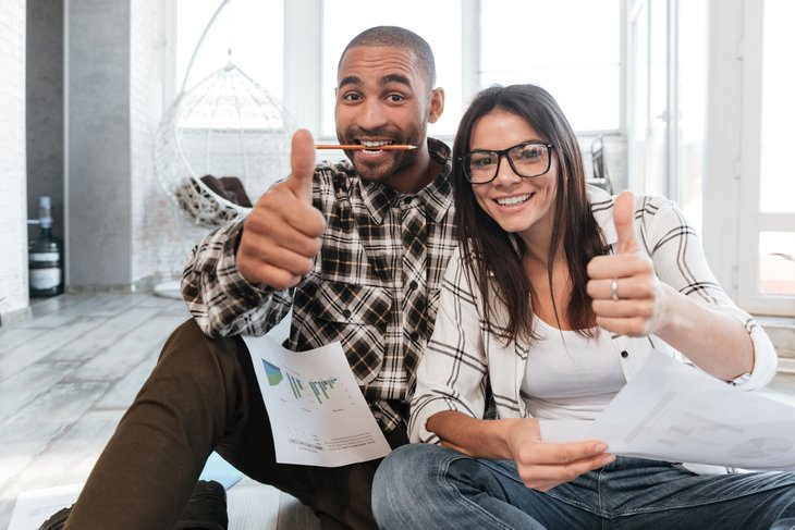 happy couple woman man working business partners documents making thumbs up