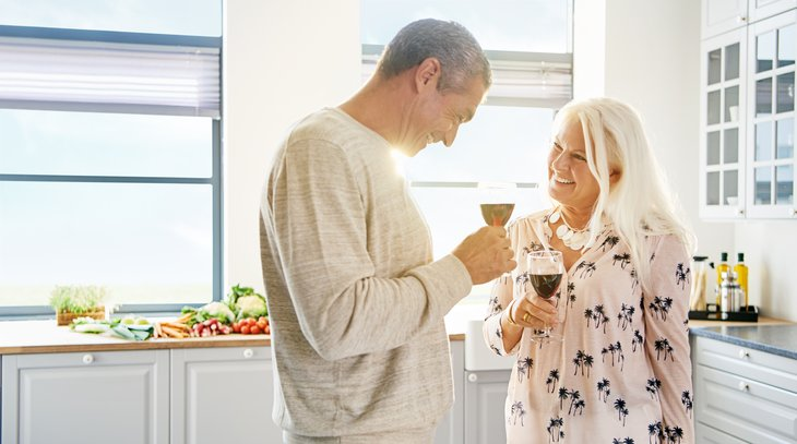 Happy retired couple red wine toast white kitchen