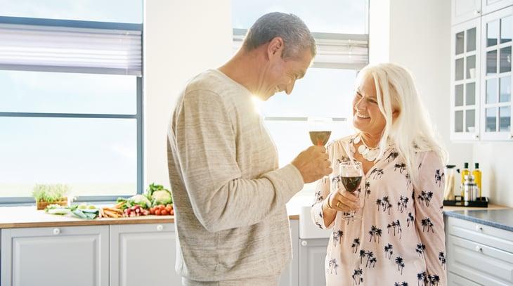 Happy retired couple red wine toast white kitchen