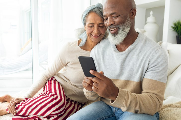 An older couple uses a smartphone