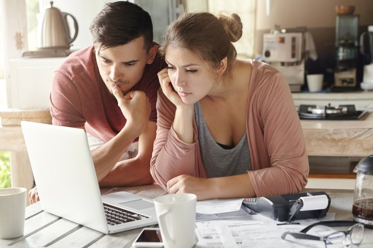 concentrating couple man and woman table laptop screen focused bills computer Family budget and finances
