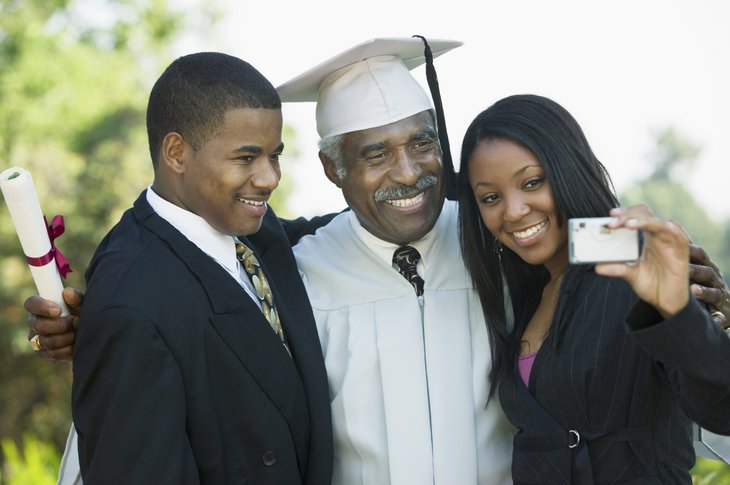 A senior black man poses for a photo at his college graduation