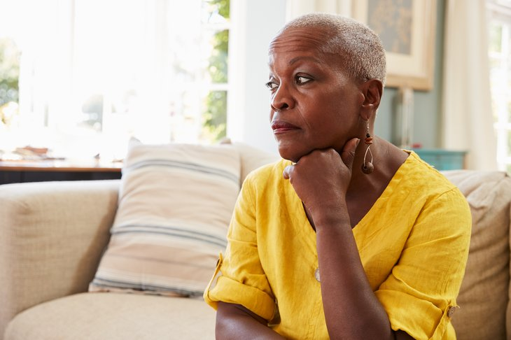 A worried senior black woman sits on her couch