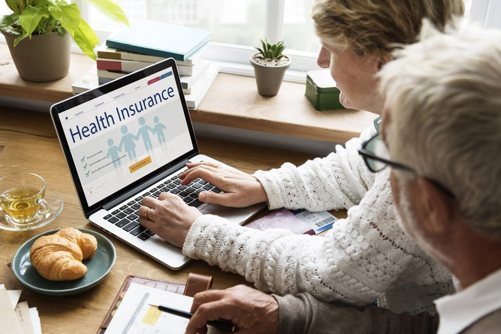 A senior couple shops for health insurance online
