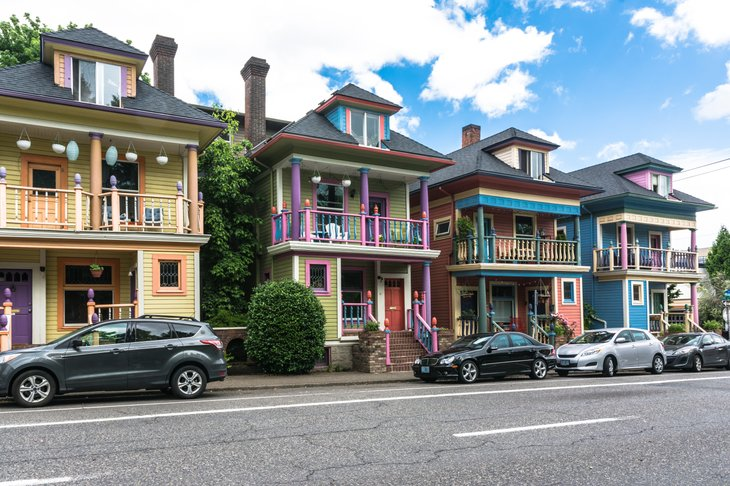 cars parked in front of a row of colorful houses