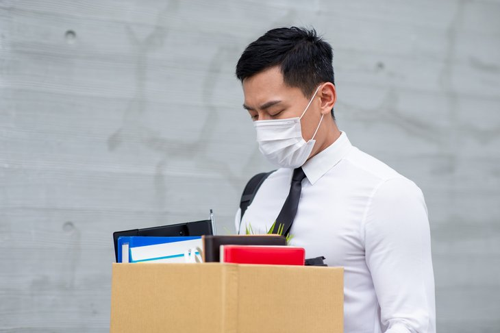 unemployed. out of work. young Asian man white shirt tie box