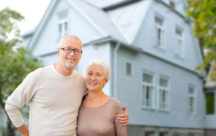 Older couple in front of a house
