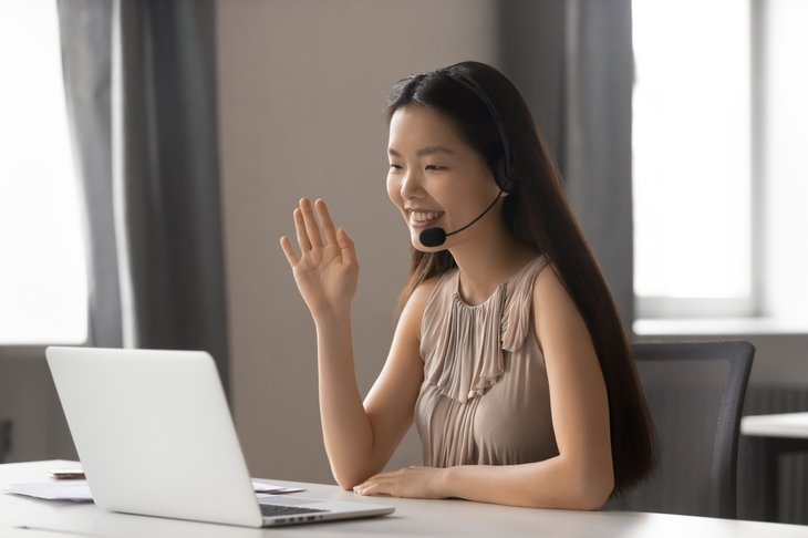 A young Asian woman wears a headset for an online meeting