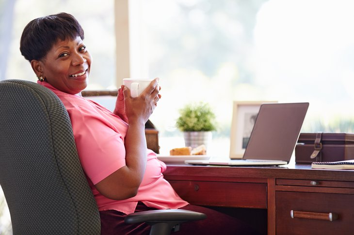 A black woman works from home over a cup of coffee