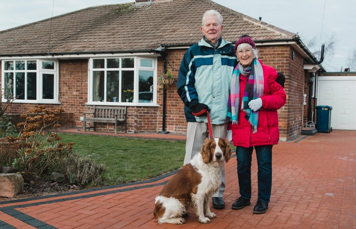 A senior couple in front of their house with their dog