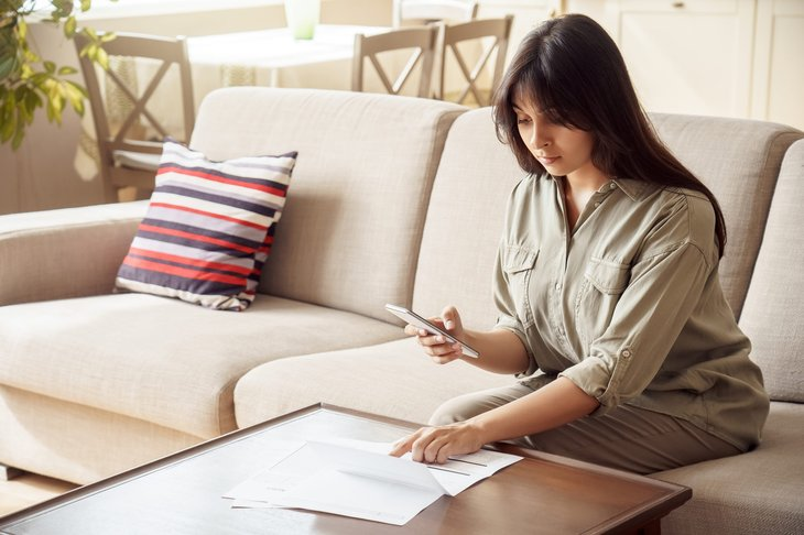 Woman checking her investments on phone and paper statement