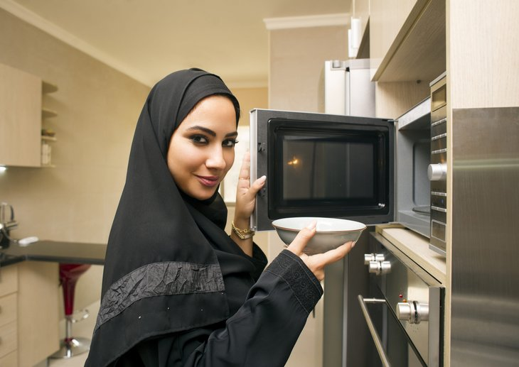 Woman in front of a microwave