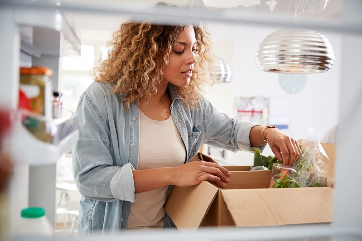 Woman unpacking a home delivery meal kit