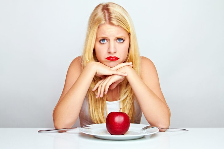 Unhappy woman with an apple