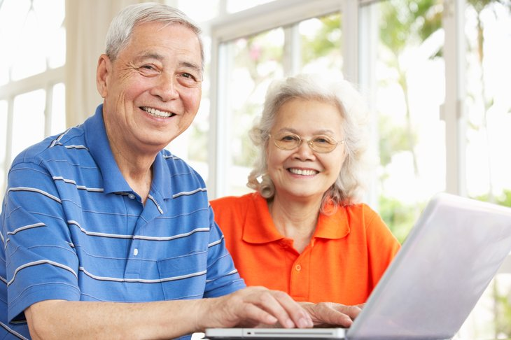 A senior Asian couple uses a laptop computer at home