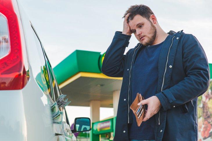 Sad man at gas pump
