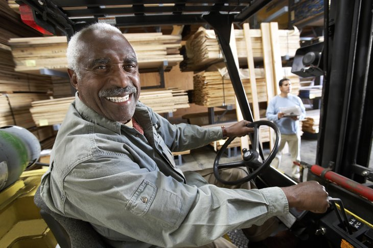 A black senior man drives a forklift at work