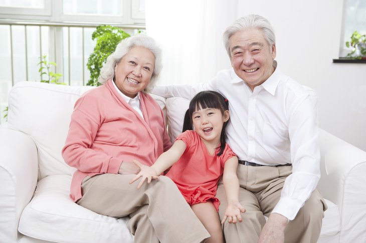 A senior Asian couple with their grandchild