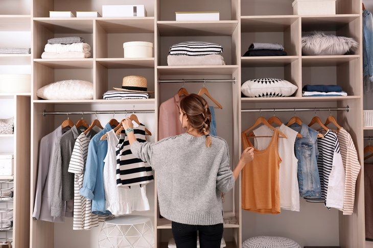 A woman picks clothes out of her closet