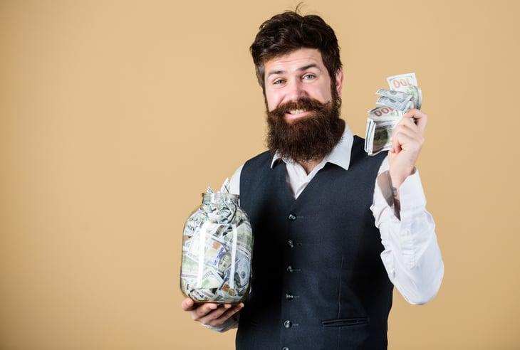 A rich man holds a big jar of cash