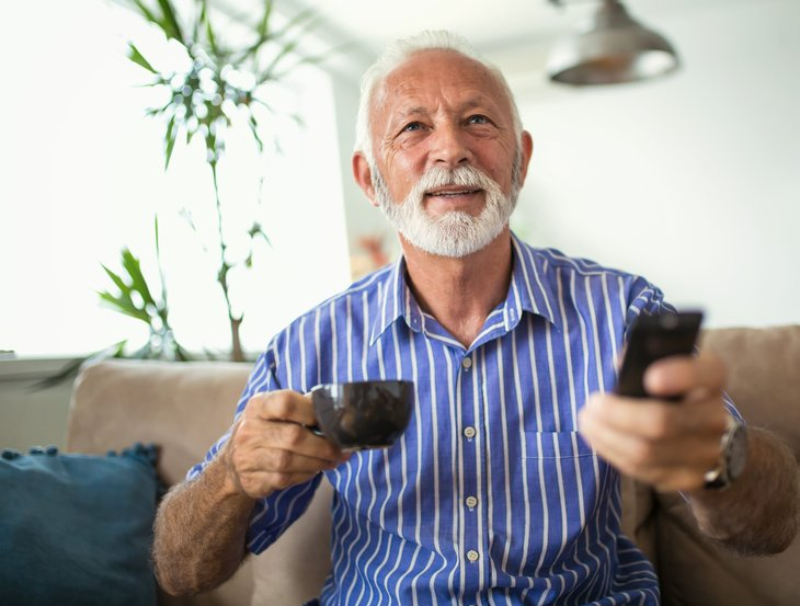 A senior man holds a remote control and coffee while watching tv on his sofa