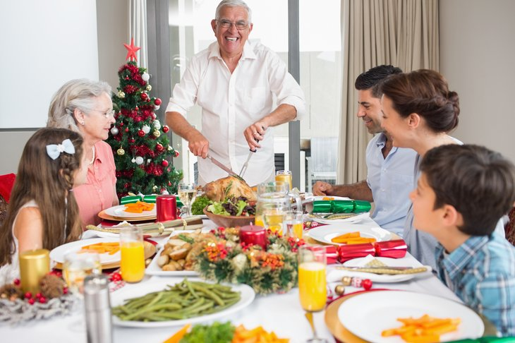 A family eats turkey for Christmas dinner