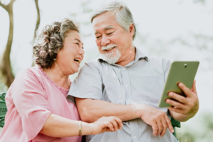 A happy senior Asian couple uses a tablet computer outdoors