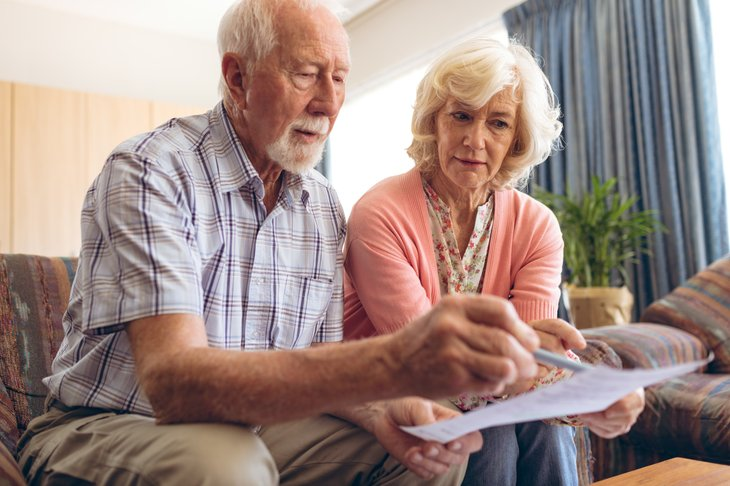 A senior couple reviews a bill
