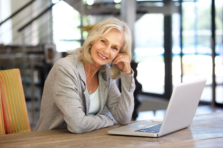 Portrait of older woman working laptop computer indoors