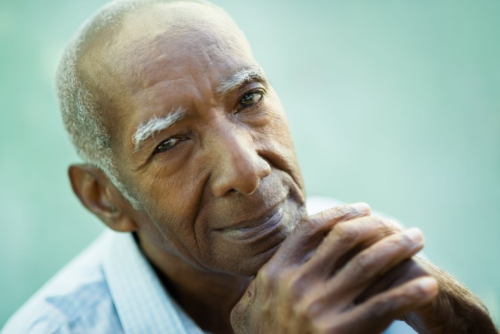 A Hispanic senior smiles and holds his hands to his chin