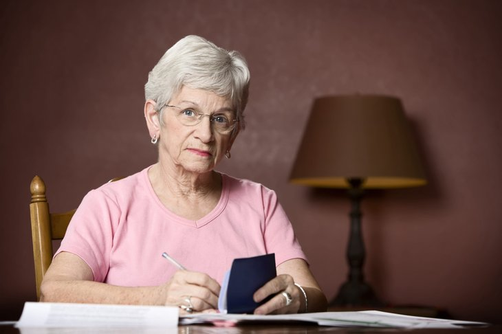 Upset senior woman writing a check