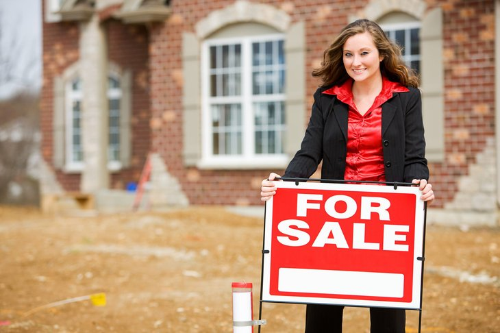 A real estate agent posts a for sale sign in front of a brick house that is under construction