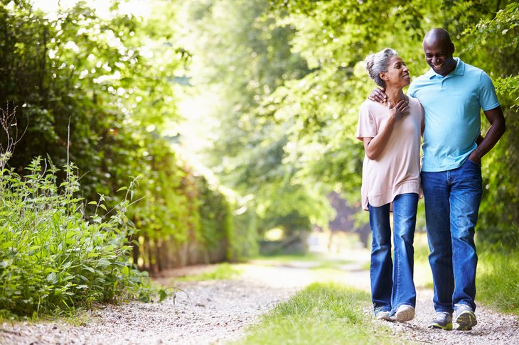 An older black couple gets exercise by walking outdoors