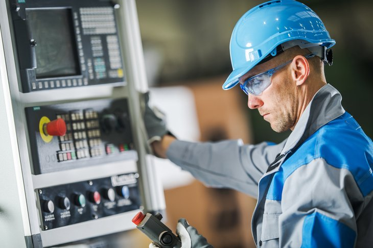A man working a control panel in a hard hat