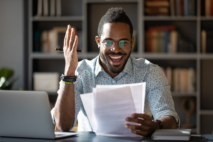 Excited man looking at documents while working from home