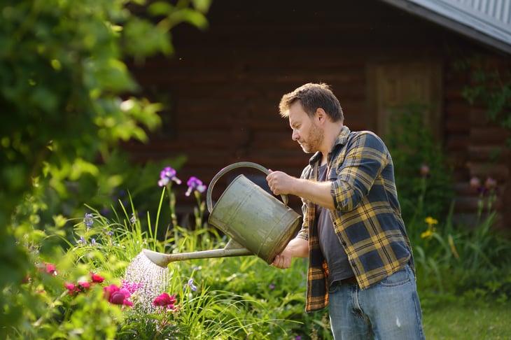 Man watering flowers in his yard