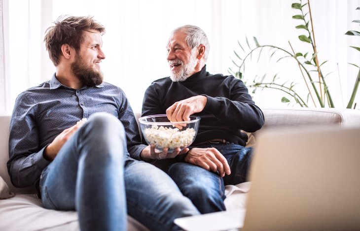 A senior father watches TV on a laptop computer with his son while eating popcorn on a sofa at home