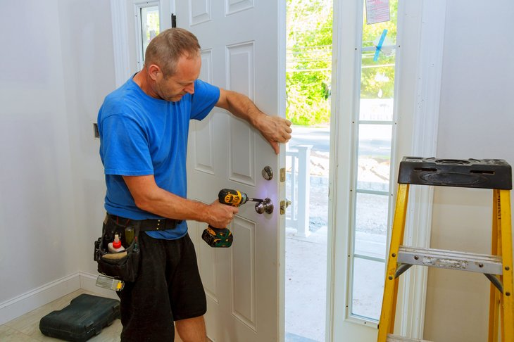 Worker installing a lock on the front door of a home