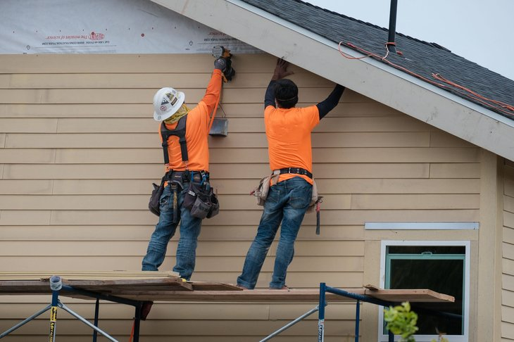 Construction workers installing vinyl siding on a house in Los Angeles, California