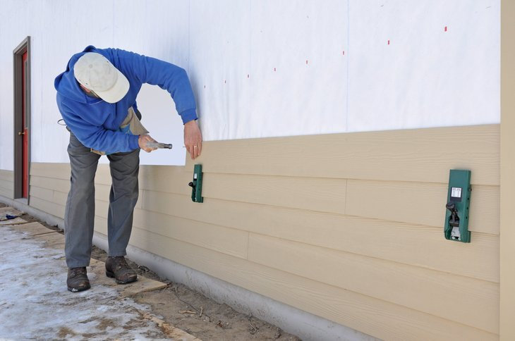 Man installing fibrous cement siding on a home