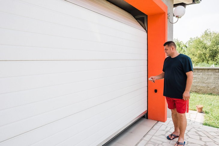 Man opening his garage door with a remote control