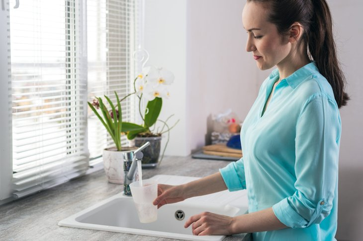 Woman filling a glass of water